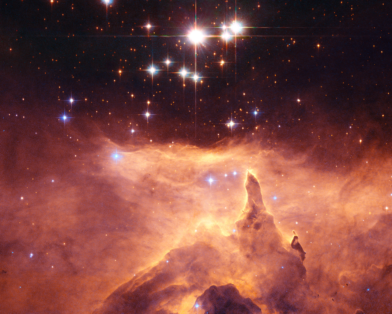 """The star cluster Pismis 24 lies in the core of the large emission nebula NGC 6357 that extends one degree on the sky in the direction of the Scorpius constellation. Part of the nebula is ionised by the youngest (bluest) heavy stars in Pismis 24. The intense ultraviolet radiation from the blazing stars heats the gas surrounding the cluster and creates a bubble in NGC 6357. The presence of these surrounding gas clouds makes probing into the region even harder. One of the top candidates for the title of """"Milky Way stellar heavyweight champion"""" was, until now, Pismis 24-1, a bright young star that lies in the core of the small open star cluster Pismis 24 (the bright stars in the Hubble image) about 8,000 light-years away from Earth. Pismis 24-1 was thought to have an incredibly large mass of 200 to 300 solar masses. New NASA/ESA Hubble measurements of the star, have, however, resolved Pismis 24-1 into two separate stars, and, in doing so, have """"halved"""" its mass to around 100 solar masses."""